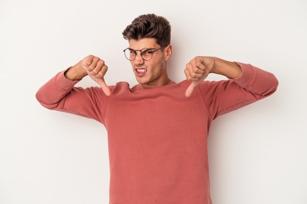 Young caucasian man isolated on white background showing thumb down, disappointment concept.