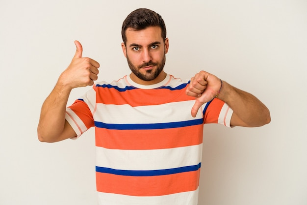Young caucasian man isolated on white background showing thumbs up and thumbs down, difficult choose concept