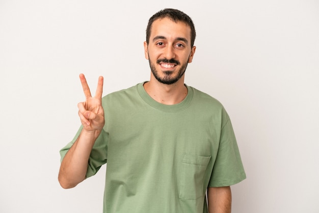 Young caucasian man isolated on white background showing victory sign and smiling broadly.