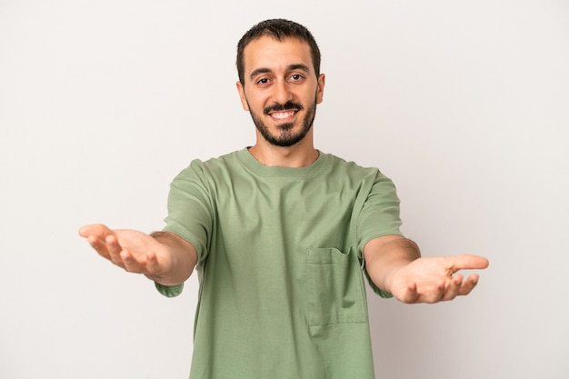 Young caucasian man isolated on white background showing a welcome expression.