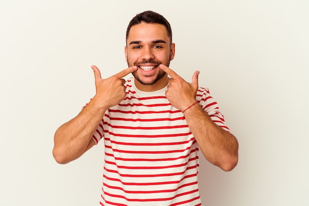 Young caucasian man isolated on white background smiles, pointing fingers at mouth.