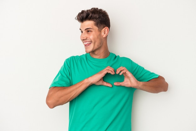 Young caucasian man isolated on white background smiling and showing a heart shape with hands.