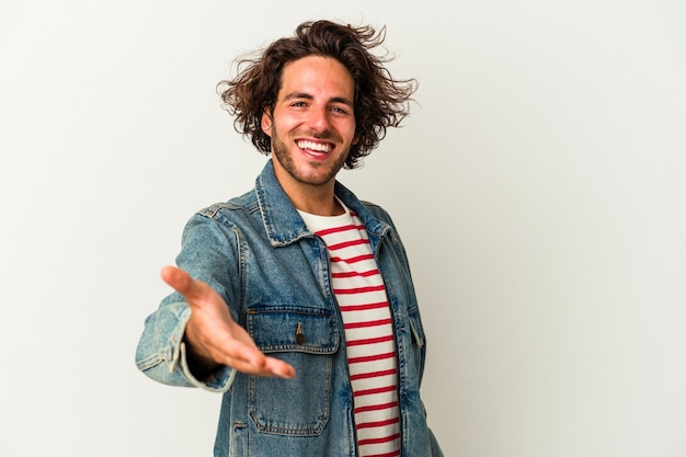 Young caucasian man isolated on white background stretching hand at camera in greeting gesture.
