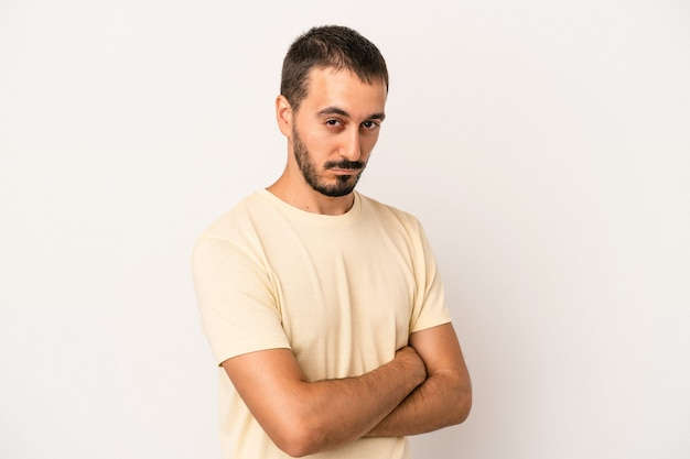 Young caucasian man isolated on white background suspicious, uncertain, examining you.