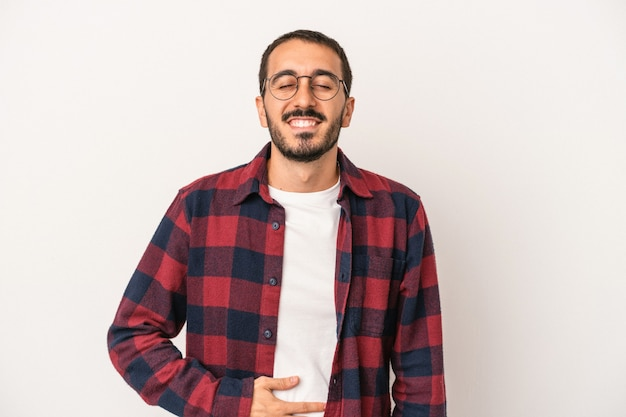 Young caucasian man isolated on white background touches tummy, smiles gently, eating and satisfaction concept.