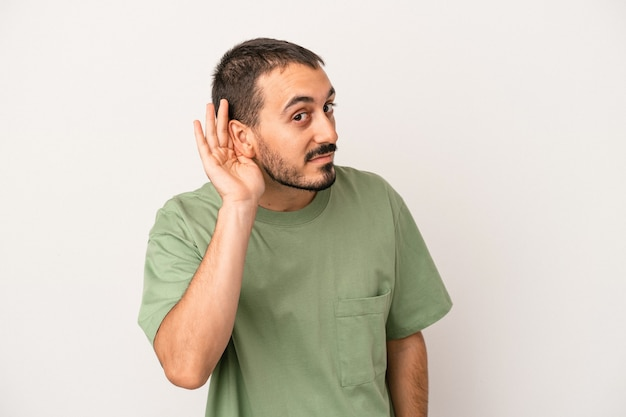 Young caucasian man isolated on white background trying to listening a gossip.