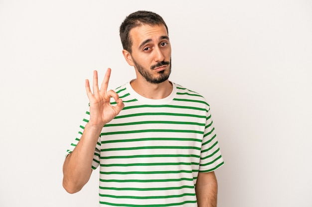 Young caucasian man isolated on white background winks an eye and holds an okay gesture with hand.