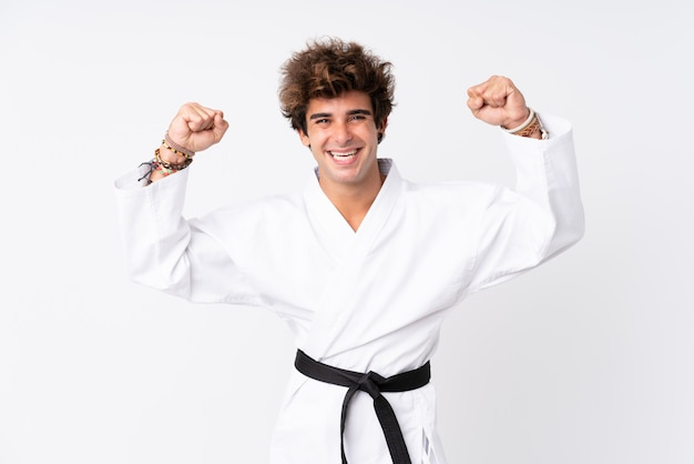 Young caucasian man over isolated white wall doing karate and making strong gesture