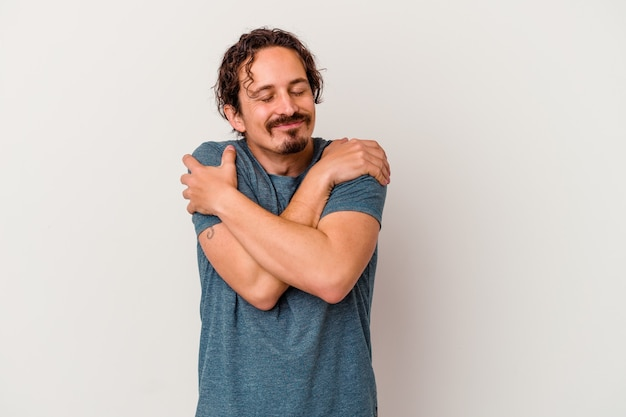 Young caucasian man isolated on white wall hugs, smiling carefree and happy.