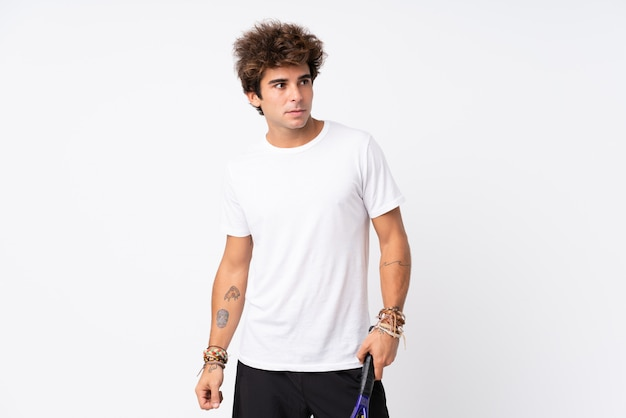 Young caucasian man over isolated white wall playing tennis