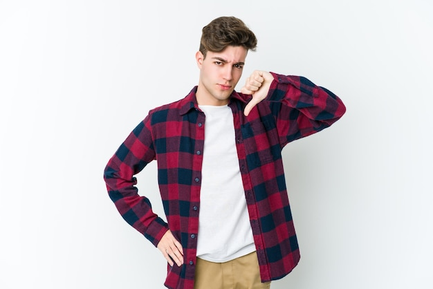 Young caucasian man isolated on white wall showing thumb down, disappointment concept.