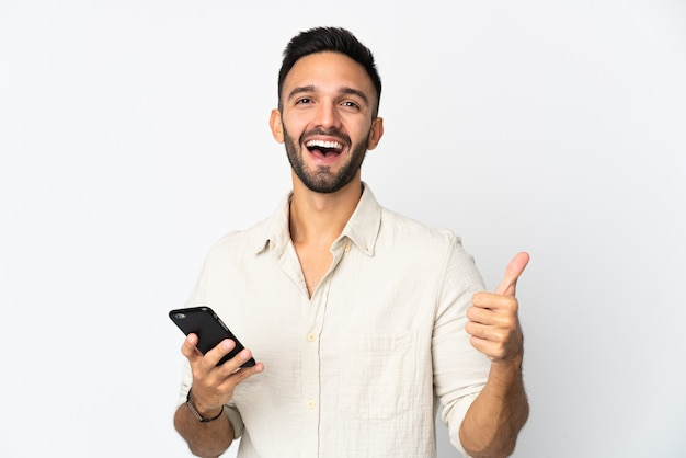 Young caucasian man isolated on white wall using mobile phone while doing thumbs up