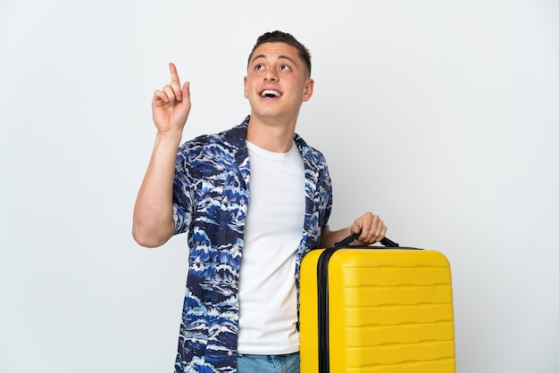 Young caucasian man isolated on white wall in vacation with travel suitcase and pointing up