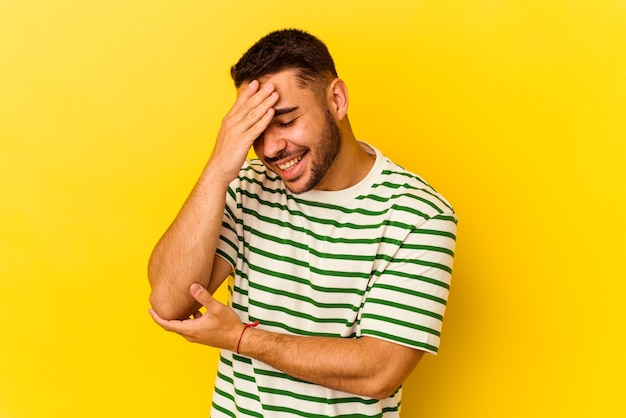 Young caucasian man isolated on yellow background blink at the camera through fingers, embarrassed covering face.