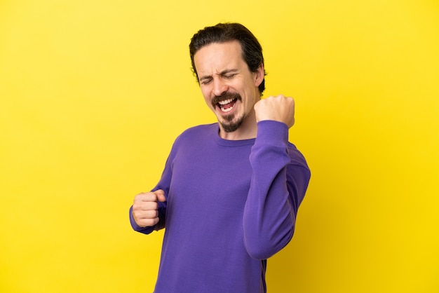 Young caucasian man isolated on yellow background celebrating a victory