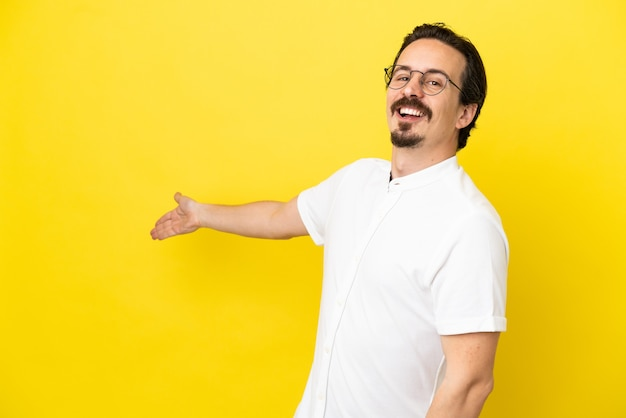 Young caucasian man isolated on yellow background extending hands to the side for inviting to come