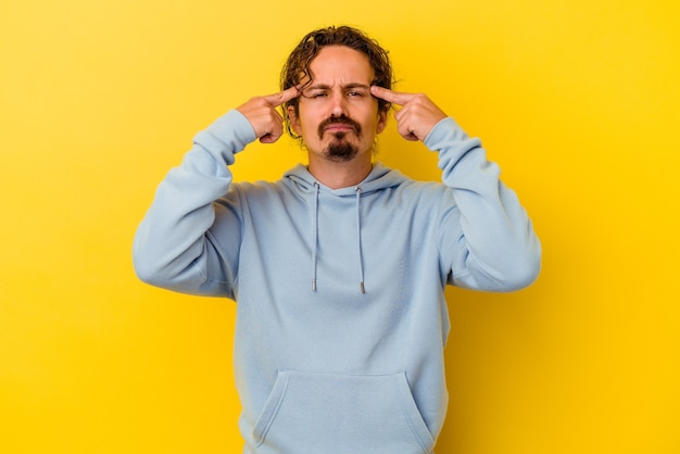 Young caucasian man isolated on yellow background focused on a task, keeping forefingers pointing head.