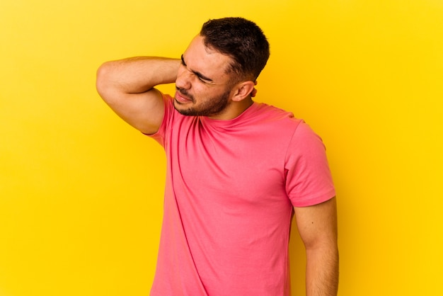 Young caucasian man isolated on yellow background having a neck pain due to stress, massaging and touching it with hand.