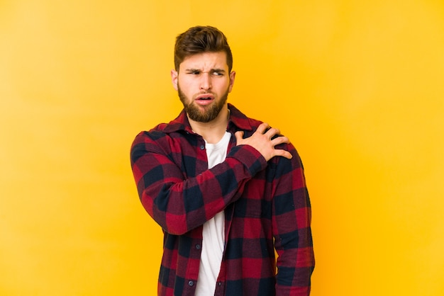 Young caucasian man isolated on yellow background having a shoulder pain.