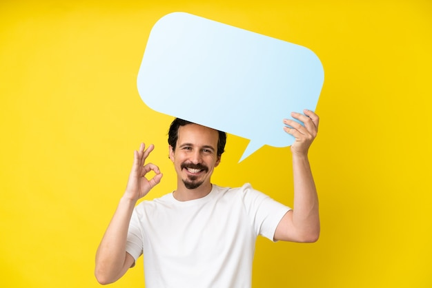 Young caucasian man isolated on yellow background holding an empty speech bubble and doing ok sign