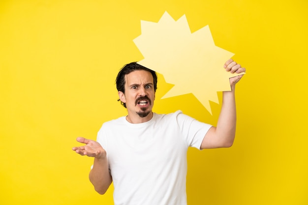 Young caucasian man isolated on yellow background holding an empty speech bubble and with frustrated expression