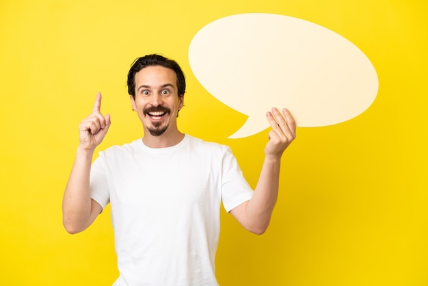 Young caucasian man isolated on yellow background holding an empty speech bubble with surprised expression