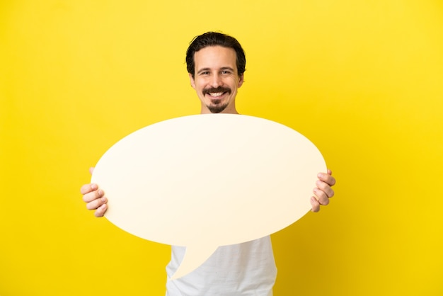 Young caucasian man isolated on yellow background holding an empty speech bubble