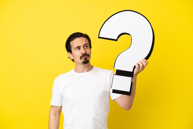 Young caucasian man isolated on yellow background holding a question mark icon and having doubts