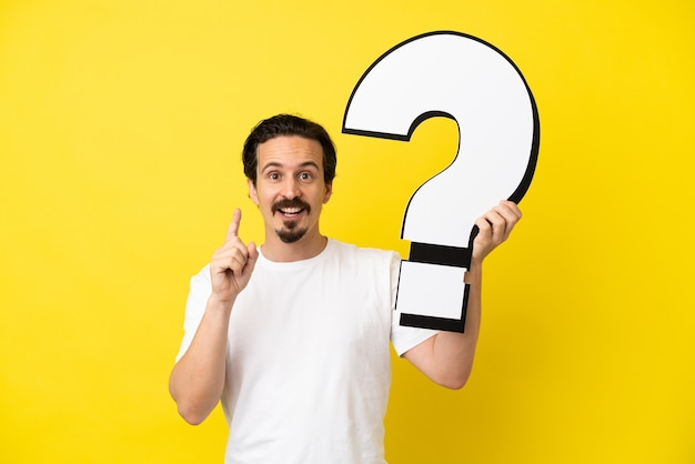 Young caucasian man isolated on yellow background holding a question mark icon