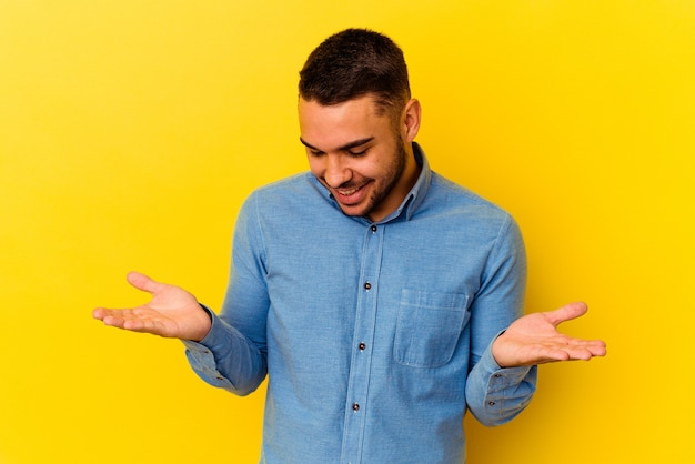 Young caucasian man isolated on yellow background holding something with palms, offering to camera.
