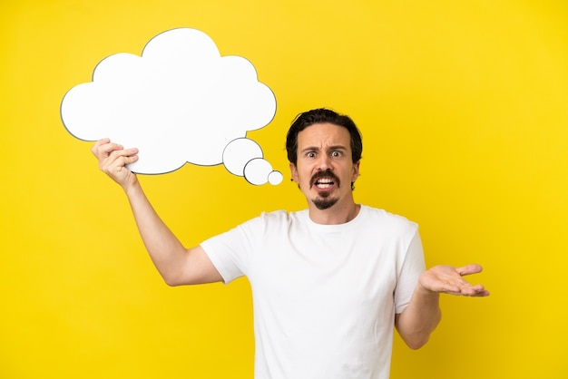 Young caucasian man isolated on yellow background holding a thinking speech bubble and with sad expression
