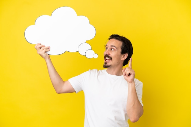 Young caucasian man isolated on yellow background holding a thinking speech bubble with surprised expression