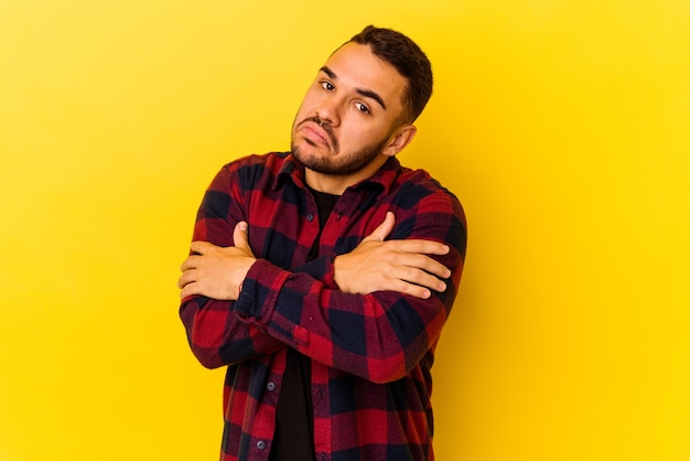 Young caucasian man isolated on yellow background hugs, smiling carefree and happy.