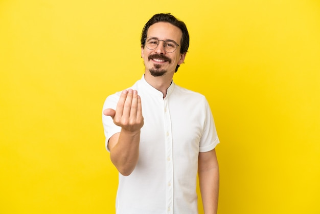 Young caucasian man isolated on yellow background inviting to come with hand. happy that you came