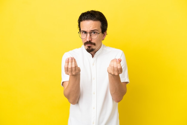 Young caucasian man isolated on yellow background making money gesture but is ruined