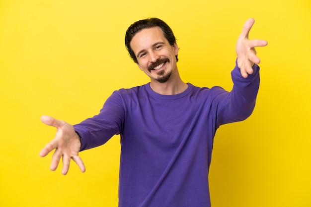 Young caucasian man isolated on yellow background presenting and inviting to come with hand