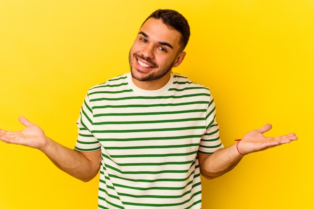 Young caucasian man isolated on yellow background showing a welcome expression.