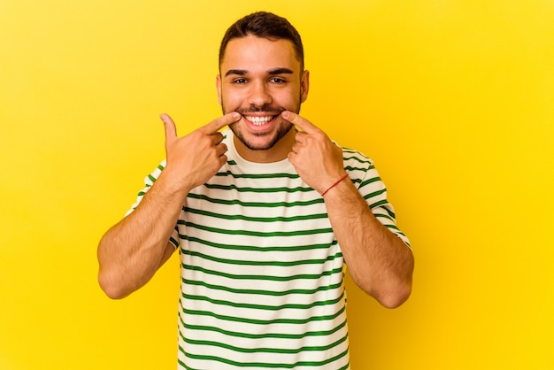 Young caucasian man isolated on yellow background smiles, pointing fingers at mouth.