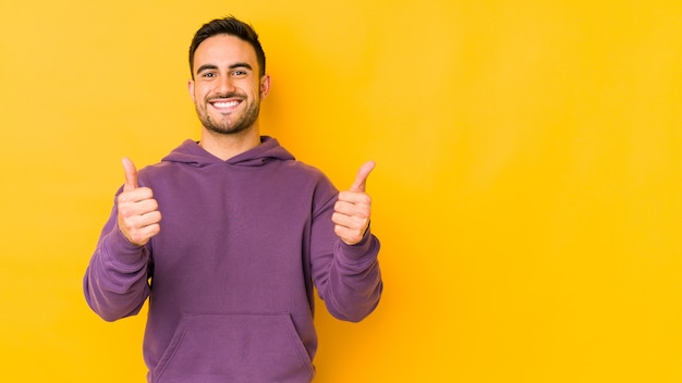 Young caucasian man isolated on yellow background smiling and raising thumb up