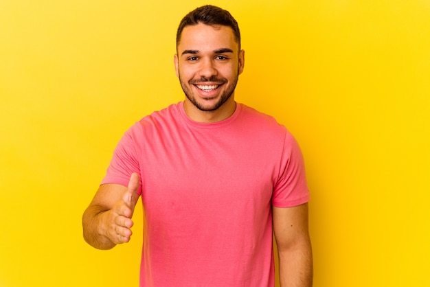 Young caucasian man isolated on yellow background stretching hand at camera in greeting gesture.