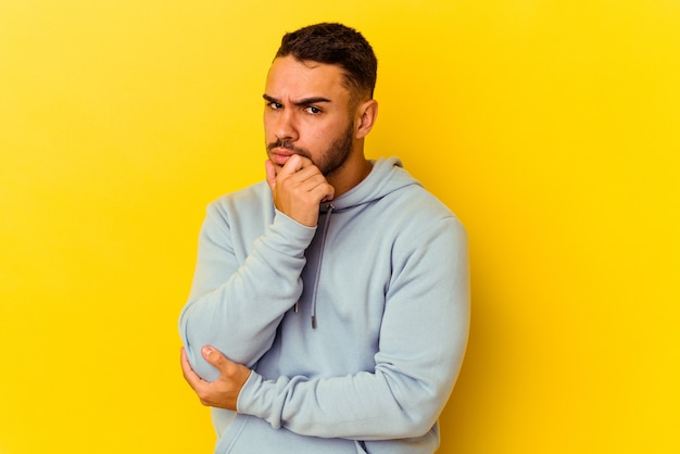 Young caucasian man isolated on yellow background suspicious, uncertain, examining you.