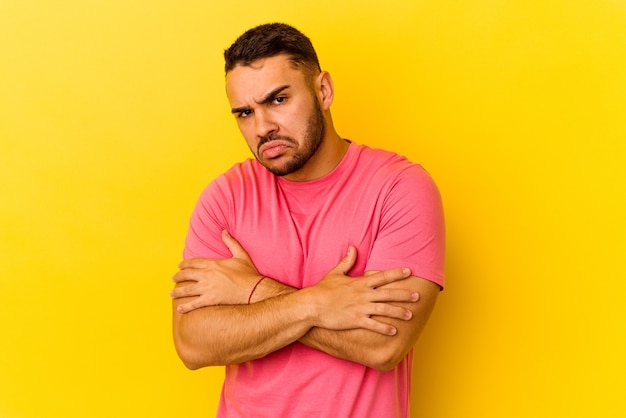 Young caucasian man isolated on yellow background unhappy looking in camera with sarcastic expression.