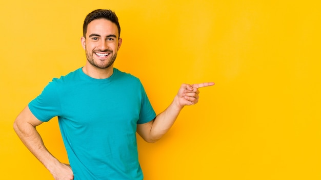 Young caucasian man isolated on yellow bakground smiling cheerfully pointing with forefinger away.