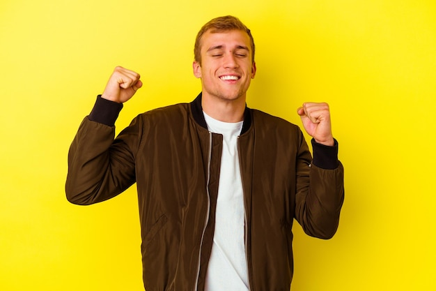 Young caucasian man isolated on yellow celebrating a victory, passion and enthusiasm, happy expression.
