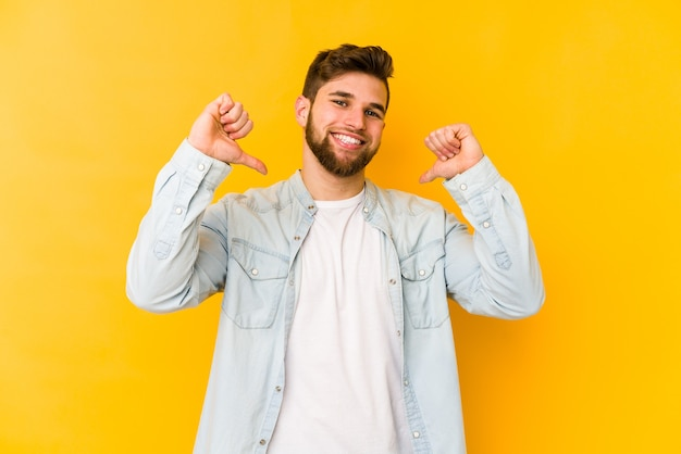 Young caucasian man isolated on yellow feels proud and self confident, example to follow.