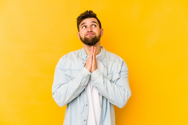 Young caucasian man isolated on yellow holding hands in pray near mouth, feels confident.