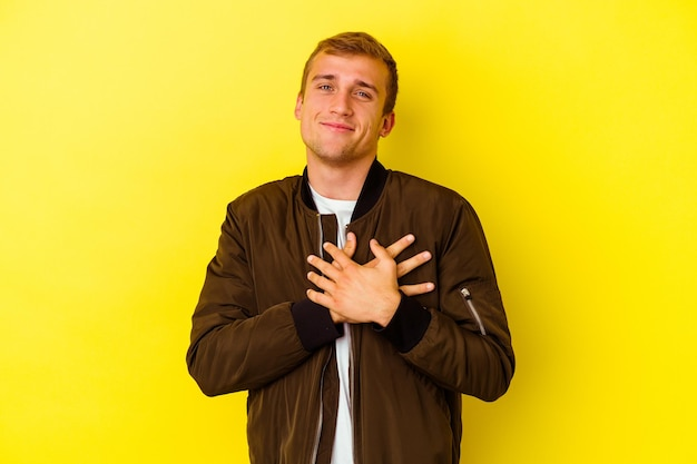 Young caucasian man isolated on yellow laughing keeping hands on heart, concept of happiness.