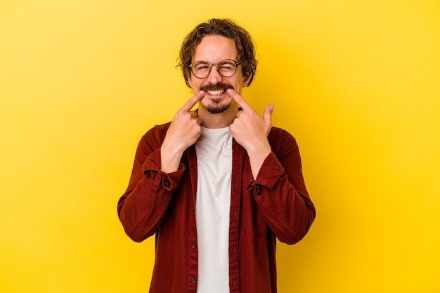 Young caucasian man isolated on yellow smiles, pointing fingers at mouth.