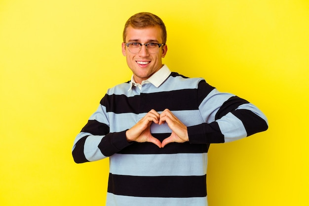 Young caucasian man isolated on yellow smiling and showing a heart shape with hands.