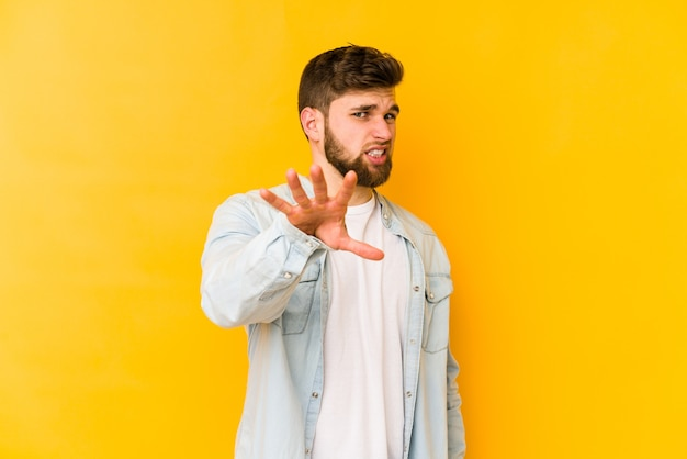 Young caucasian man isolated on yellow space rejecting someone showing a gesture of disgust.